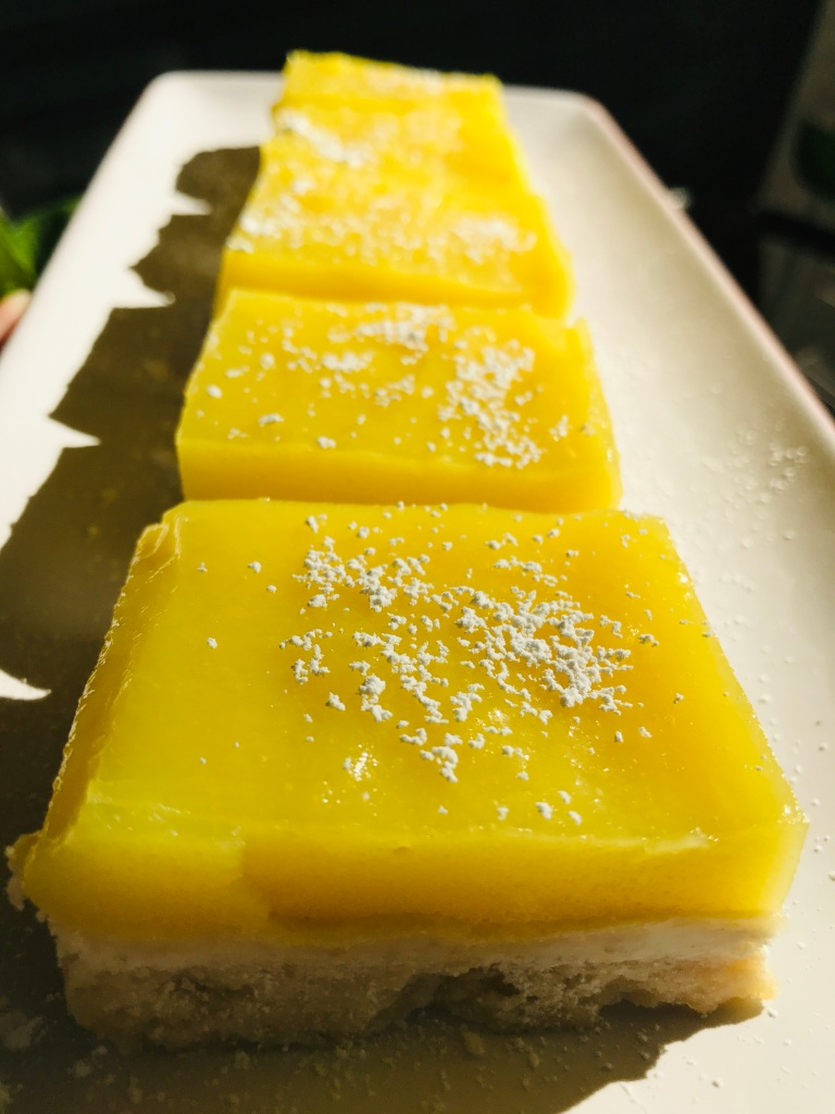Close-up image of vegan lemon bar square with powdered sugar on a plate