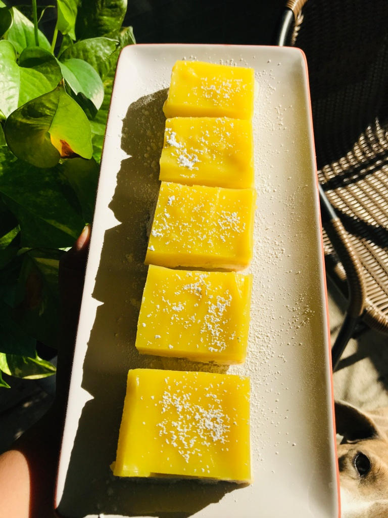vegan lemon bar squares with powdered sugar on a plate
